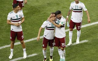 Mexico's Oribe Peralta embraces teammate Andres Guardado as Raul Jimenez, left, and Jesus Corona, right, watch following their 2-1 win over South Korea in their group F match at the 2018 soccer World Cup in the Rostov Arena in Rostov-on-Don, Russia, Saturday, June 23, 2018. (AP Photo/Efrem Lukatsky)