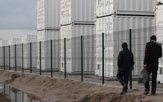 People walk past containers placed at the entrance of the Calais refugee camp, northern France, Monday, Jan. 11, 2016. Approximately 130 containers will be converted to shelters to accommodate as many as 1,500 migrants who are expected to move in on Jan. 11, 2016. (AP Photo/Michel Spingler)