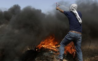 Palestinians hurl stones and burn tires near the fence of the Gaza Strip's border with Israel, during a protest east of Khan Younis, in the Gaza Strip, Friday, June 8, 2018. Palestinians burned tires and Israeli troops fired heavy volleys of tear gas Friday to push back large Gaza crowds from the area of the fence separating the blockaded territory from Israel. (AP Photo/Adel Hana)