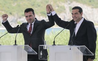 Greek Prime Minister Alexis Tsipras, right and his Macedonian counterpart Zoran Zaev, raise their hands during a signing agreement for Macedonia's new name in the village of Psarades, Prespes Greece, on Sunday, June 17, 2018. The preliminary deal launches a long process that will last several months. If successful, it will end a decades-long dispute between neighbors Greece and Macedonia _ which will be renamed North Macedonia. (AP Photo/Yorgos Karahalis)