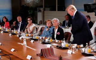 Christine Lagarde, the Managing Director of the International Monetary Fund, German Chancellor Angela Merkel, Dayle Haddon and other leaders react as U.S. President Donald Trump shows up late to the Gender Equality Advisory Council breakfast working during the G-7 summit in the Charlevoix city of La Malbaie, Quebec, Canada, June 9, 2018. REUTERS/Leah Millis