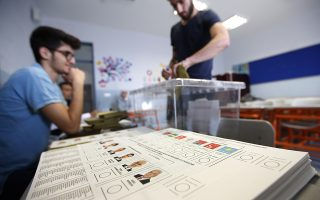 Ballot papers lie on a table as a man cats his vote in Turkey's elections at a polling station in Istanbul, Sunday, June 24, 2018. Turkish voters are voting Sunday in a historic double election for the presidency and parliament. (AP Photo/Lefteris Pitarakis)