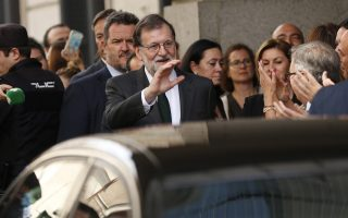 Spain's Prime Minister Mariano Rajoy waves on leaving the parliament after a motion of no confidence vote at the Spanish parliament in Madrid, Friday, June 1, 2018. Opposition Socialist leader Pedro Sanchez has won the vote to replace Mariano Rajoy as prime minister, in the first ouster of a serving Spanish leader by parliament in four decades of democracy. (AP Photo/Francisco Seco)