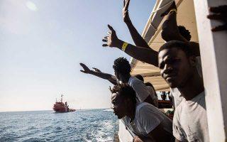 Επευφημίες μεταναστών που επιβαίνουν σε πλοιάριο της ΜΚΟ Proactiva Open Arms καθώς πλησιάζουν στο λιμάνι της Βαρκελώνης.