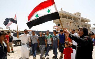 Γυναίκα υψώνει τη συριακή σημαία, πανηγυρίζοντας για την προώθηση του κυβερνητικού στρατού στην Ντεράα, στο νοτιοδυτικό τμήμα της χώρας.