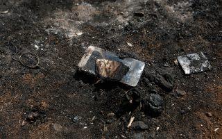 Καμένη συσκευή κινητού τηλεφώνου ανάμεσα στις στάχτες.