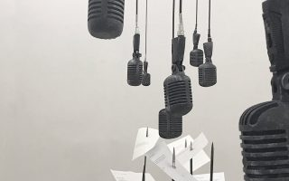 Το έργο αποτελείται από 100 μικρόφωνα, τα οποία αιωρούνται πάνω από ισάριθμες σελίδες τρυπημένες από μεταλλικά καρφιά.