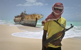 FILE - In this Sunday, Sept. 23, 2012 file photo, masked Somali pirate Hassan stands near a Taiwanese fishing vessel that washed up on shore after the pirates were paid a ransom and released the crew, in the once-bustling pirate den of Hobyo, Somalia. A U.N. official said Friday, Feb. 27, 2015 that Somali pirates have released four Thai sailors who were held hostage for nearly five years, after their ship the FV Prantalay 12 was seized by Somali pirates on April 18, 2010. (AP Photo/Farah Abdi Warsameh, File)