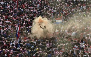 A Croatian national soccer fan lights a flare in celebration after his team had scored a goal in the World Cup final,  in central Zagreb, Croatia, Sunday, July 15, 2018. Croatia's national soccer team faces France in the World Cup final in Russia. (AP Photo/Marko Drobnjakovic)