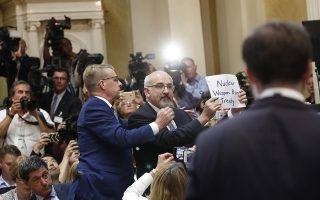 An individual, seated with the American press corps in Helsinki, holds a sign about nuclear weapons, prior to the beginning of a joint news conference with U.S. President Donald Trump and Russian President Vladimir Putin at the Presidential Palace in Helsinki, Finland, Monday, July 16, 2018.   (AP Photo/Pablo Martinez Monsivais)