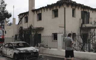 A man stands outside a burned-out house in the village of Neos Voutzas near Athens, Tuesday, July 24, 2018. Greece sought international help through the European Union as fires on either side of Athens left lines of cars torched, charred farms and forests, and sent hundreds of people racing to beaches to be evacuated by navy vessels, yachts and fishing boats.(AP Photo/Yorgos Karahalis)