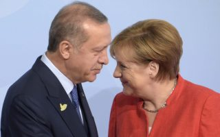 Turkish President Recep Tayyip Erdogan, left, is welcomed by German Chancellor Angela Merkel on the first day of the G-20 summit in Hamburg, northern Germany, Friday, July 7, 2017. The leaders of the group of 20 meet July 7 and 8. (AP Photo/Jens Meyer)