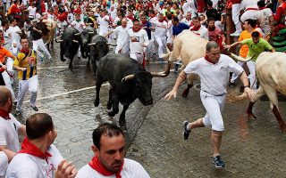 epa06873253 The runners dodge the bulls of the cattle ranch of Jose Escolar Gil (Avila) during the second day of the Festival of San Fermin 2018 in Pamplona, Spain, 08 July 2018. The festival, locally known as Sanfermines, is held annually from 06 to 14 July in commemoration of the city's patron saint. Hundreds of thousands of visitors from all over the world attend the fiesta.  EPA/DANIEL FERNANDEZ