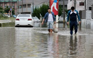 epa06870271 Residents walk a road flooded by heavy rain in Kurume, Fukuoka Prefecture, western Japan, 07 July 2018. Heavy rainfall killed 38 people and missing about 50 people in southwestern and western Japan, public television reported on 07 July 2018. Japan Meteorological Agency has warned record rainfall on 06 July for flooding, mudslides in southwestern and western Japan through 08 July and issued emergency weather warnings to six prefectures. In nine prefectures in western and southwestern Japan,  authorities issued evacuation orders to more than one million of people in southwestern and western Japan.  EPA/JIJI PRESS EDITORIAL USE ONLY/NO ARCHIVE/JAPAN OUT  NO ARCHIVES