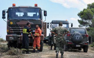 Πυροσβέστες και εθελοντές δασοπυροσβέστες από την Κύπρο δίπλα σε οχήματα οχήματα του 747 Ειδικού Τάγματος Μηχανικού Λουτρακίου, σε αναμονή στην περιοχή μεταξύ των Αγίων Θεοδώρων και Λουτρακίου, όπου παρακολουθούν το μέτωπο της πυρκαγιάς που είναι σε πλήρη εξέλιξη και κατακαεί από τη Δευτέρα τα Γεράνεια Όρη, Τετάρτη 25 Ιουλίου 2018. Η φωτιά καίει πευκόφυτη χαράδρα, ενώ οι πυροσβέστες δυσκολεύονται να προσεγγίσουν το σημείο με τα πυροσβεστικά οχήματα, λόγω της έλλειψης δασικών δρόμων. ΑΠΕ-ΜΠΕ/ΑΠΕ-ΜΠΕ/ΒΑΣΙΛΗΣ ΨΩΜΑΣ