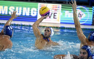Evangelos Ioannis Delakas, center, of Greece prepares to pass the ball past Denes Varga of Hungary during the men's water polo semifinal match Greece vs. Hungary at the 17th FINA Swimming World Championships in Hajos Alfred National Swimming Pool in Budapest, Hungary, Thursday, July 27, 2017. (Szilard Koszticsak/MTI via AP)