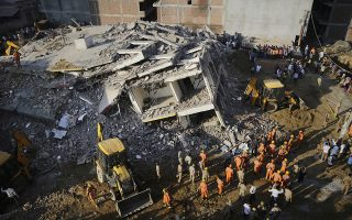 Rescuers work at the site of a building collapsed in Shahberi village, east of New Delhi, India, Wednesday, July 18, 2018. The six-story building under construction collapsed onto an adjacent building. (AP Photo/Altaf Qadri)
