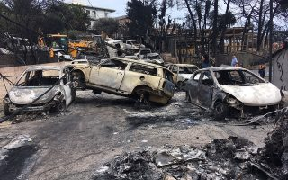 Tα απανθρακωμένα αυτοκίνητα μπροστά στην «Αργυρή Ακτή», χθες, το πρωί.