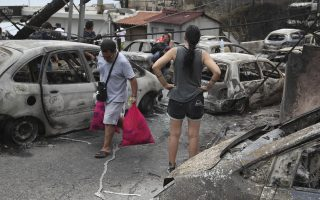 People walk amongst the burned-out cars in Mati east of Athens, Tuesday, July 24, 2018. Twin wildfires raging through popular seaside areas near the Greek capital have torched homes, cars and forests and killed at least 49 people, authorities said Tuesday, raising the death toll after rescue crews reported finding the bodies of more than 20 people huddled together near a beach. (AP Photo/Thanassis Stavrakis)