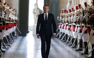 French President Emmanuel Macron walks through the Galerie des Bustes (Busts Gallery) to access the Versailles Palace's hemicycle to address both the upper and lower houses of the French parliament at a special session in Versailles, near Paris, Monday, July 9, 2018. Macron is convening both houses of parliament to review his first year in office and lay out his plans for his mandate's next four years. (Charles Platiau/Pool via AP)