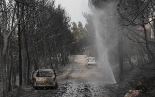 Burned-out cars destroyed in the wildfires line a road near the village of Neos Voutzas near Athens, Tuesday, July 24, 2018. Greece sought international help through the European Union as fires on either side of Athens left lines of cars torched, charred farms and forests, and sent hundreds of people racing to beaches to be evacuated by navy vessels, yachts and fishing boats.(AP Photo/Yorgos Karahalis)