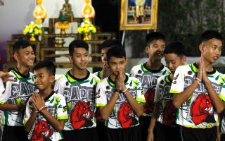 epa06896322 Some of the 12 members of the Wild Boar soccer team, who were rescued from the Tham Luang cave, greet the media during a military governmental TV pool broadcasting program at Chiang Rai Provincial Administrative Organization in Chiang Rai province, Thailand, 18 July 2018. The thirteen members of Wild Boar child soccer team, including their assistant coach, who were trapped in the Tham Luang cave since 23 June 2018, made their first appearance on the day for a tightly-controlled interview with the media after they were rescued, before returning to their homes with families.  EPA/PONGMANAT TASIRI