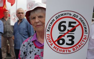 An elderly woman holds a poster reads
