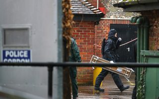 Police officers in black protective suits arrive with new equipment in the cordoned off area around The Mill public house, which had been visited by Sergei Skripal, in Salisbury, Britain, April 4, 2018. REUTERS/Hannah McKay