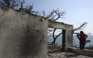 A member of a rescue team searches a burned house in Mati, east of Athens, Wednesday, July 25, 2018. Rescue crews were searching Wednesday through charred homes and cars for those still missing after the deadliest wildfires to hit Greece in decades decimated seaside areas near Athens, killing at least 79 people and sending thousands fleeing. (AP Photo/Thanassis Stavrakis)
