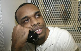 In this June 13, 2018, photo, death-row inmate Christopher Young holds a phone to his ear during an interview outside death row at the Texas Department of Criminal Justice Polunsky Unit near Livingston, Texas. The Texas Court of Criminal Appeals has refused to stop the scheduled execution of Young, who was convicted of fatally shooting San Antonio convenience store owner Hasmukh