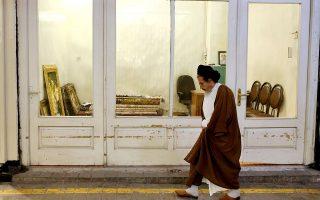 Ιρανός κληρικός περνάει μπροστά από παραδοσιακό κατάστημα. Η χώρα μοιάζει να αψηφά τις απειλές Τραμπ.