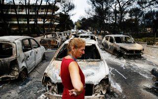 Η θλίψη αποτυπώνεται στο πρόσωπο της γυναίκας αυτής καθώς περνάει τη μακρά σειρά από καμένα αυτοκίνητα στο Μάτι.