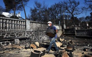 Ανδρας καθαρίζει την αυλή σπιτιού που καταστράφηκε από τη φονική πυρκαγιά της 23ης Ιουλίου.