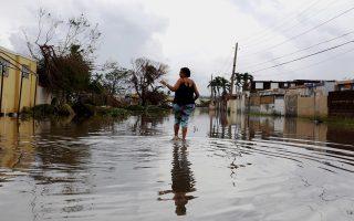 Γυναίκα βαδίζει στους πλημμυρισμένους δρόμους της Τόα Μπάχα, στις 21 Σεπτεμβρίου 2017, λίγες ώρες μετά το πέρασμα του τυφώνα «Μαρία».