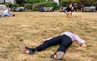 Εξαντλημένοι από τη ζέστη, οι Λονδρέζοι δεν βρίσκουν δροσιά ούτε στο «κίτρινο» Trinity Square Gardens, ένα από τα πάρκα του Λονδίνου που ξεράθηκαν λόγω της παρατεταμένης ανομβρίας. © Peter Dench/Getty Images/Ideal Image