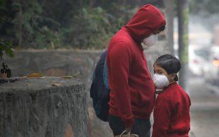 Πατέρας και κόρη προστατεύονται από την έντονη ατμοσφαιρική ρύπανση στο Νέο Δελχί με τη βοήθεια μάσκας.