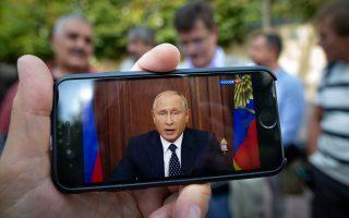 Μοσχοβίτες παρακολουθούν, μέσω κινητού τηλεφώνου, το τηλεοπτικό διάγγελμα του προέδρου Πούτιν.