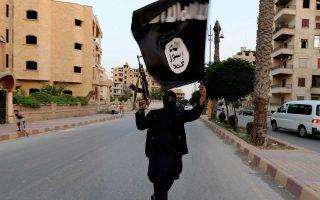 Μαχητής του Ι.Κ. κραδαίνει σημαία του «χαλιφάτου» σε δρόμο της Ράκα στη Συρία το 2014.