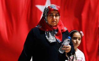 Η κυρία και το κοριτσάκι εικονίζονται μπροστά από την τουρκική σημαία – μία από τις πολυάριθμες που γέμισαν την Κωνσταντινούπολη, με φόντο τη ρήξη με τις ΗΠΑ.