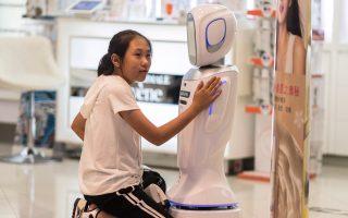 Κοριτσάκι συνεννοείται με ρομπότ-πωλητή σε κατάστημα στην Κίνα.