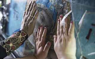 Χάδι στην αγαπημένη. Με τα χέρια απλωμένα, πιστές χαϊδεύουν το τζάμι που προστατεύει την εικόνα της Μητέρας. Στην εκκλησία Mostorod της Αιγύπτου οι χριστιανοί γιόρτασαν τα γενέθλια της Παναγίας.  EPA/MOHAMED HOSSAM