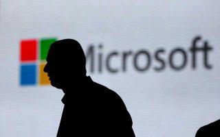 Η σιλουέτα ενός περαστικού διαγράφεται μπροστά από το εμπορικό σήμα της Microsoft στο Νέο Δελχί της Ινδίας.
