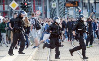 Αστυνομικοί τρέχουν στο κέντρο του Χέμνιτς για να αποτρέψουν τα πογκρόμ κατά μεταναστών από ακροδεξιούς διαδηλωτές.