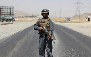 An Afghan Police officer mans a checkpoint on the Ghazni highway, in Maidan Shar, west of Kabul, Afghanistan, Monday, Aug. 13, 2018. Afghan Defense Minister Gen. Tareq Shah Bahrami said Monday that about 100 policemen and soldiers as well as 20 civilians have been killed in past four days of battle in the eastern capital of Ghazni. (AP Photo/Rahmat Gul)