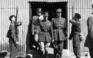 Δύο Γάλλοι σκοποί χαιρετούν με τα όπλα τους τον βασιλιά Γεώργιο ΣΤ' του Ηνωμένου Βασιλείου και τον στρατηγό Σαρλ Ντε Γκωλ, οι οποίοι εξέρχονται από τους στρατώνες των δυνάμεων της Ελεύθερης Γαλλίας, του αντιστασιακού κινήματος που δημιούργησε ο Γάλλος στρατηγός μετά την πτώση της χώρας στο Τρίτο Ράιχ, σε κάποια περιοχή της νότιας Αγγλίας, το 1940. Ήταν η πρώτη επίσκεψη του βασιλιά στις δυνάμεις των μαχόμενων Γάλλων. (AP Photo)