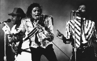 O «Βασιλιάς της Ποπ», Μαικλ Τζάκσον, μαζί με τα αδέρφια του Τίτο και Μάρλον, όλοι τους μέλη του οικογενειακού συγκροτήματος της οικογένειας Τζάκσον, «The Jackson 5», στην εναρκτήρια συναυλία της περιοδείας «Victory» του συγκροτήματος, στο Μπάφαλο της Νέας Υόρκης, το 1984. (AP Photo/Rob McElroy)