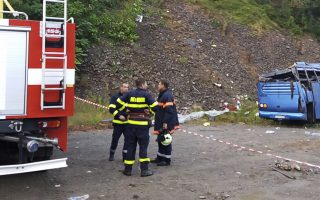 In this handout photo provided by the Bulgarian Interior Ministry, firefighters near the scene where a bus crashed and overturned, near the town of Svoge, Saturday, Aug. 25, 2018.  Bulgaria's health minister says a tourist bus has flipped over on a highway near Sofia, the capital, killing at least 15 people and leaving 27 others injured. Police said a bus carrying tourists on a weekend trip to a nearby resort overturned and then fell down a side road 20 meters (66 feet) below the highway. (Bulgarian Interior Ministry via AP)