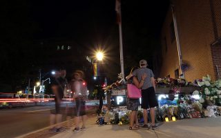 Fredericton residents pay their respects at a makeshift shrine created in front of police headquarters after four people, including two police officers, were killed in a shooting in Fredericton, the capital of the province of New Brunswick, Canada, August 10, 2018. REUTERS/Dan Culberson