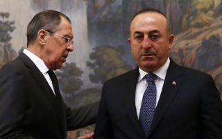 Russian Foreign Minister Sergey Lavrov, right, and Turkey's Foreign Minister Mevlut Cavusoglu attend a ceremony in memory of Russian Ambassador to Turkey Andrei Karlov, who was fatally shot by a Turkish policeman Monday at a gathering in Ankara, Turkey, before their talks on Syria in Moscow, Russia, Tuesday, Dec. 20, 2016. (Maxim Shemetov/Pool Photo via AP)