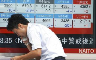 A woman walks past an electronic stock board showing Japan's Nikkei 225 index at a securities firm Tuesday, Aug. 21, 2018, in Tokyo. Asian shares are mixed amid doubts on the prospects for resolving the trade dispute between the U.S. and China. (AP Photo/Eugene Hoshiko)